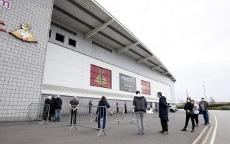 DONCASTER, ENGLAND - MARCH 06: Patients form a socially distanced queue before receiving a Covid 19 Vaccine outside the stadium prior to the Sky Bet League One match between Doncaster Rovers and Plymouth Argyle at Keepmoat Stadium on March 06, 2021 in Doncaster, England. Sporting stadiums around the UK remain under strict restrictions due to the Coronavirus Pandemic as Government social distancing laws prohibit fans inside venues resulting in games being played behind closed doors. (Photo by George Wood/Getty Images)