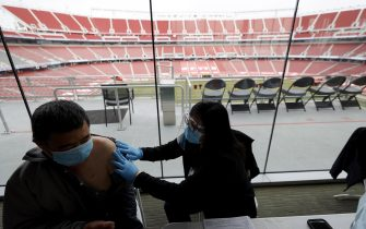 SANTA CLARA, CALIFORNIA - FEBRUARY 09: Xiangheng Liu, 69, (L) of San Jose prepares to receive a COVID-19 vaccination on the opening day of a mass COVID-19 vaccination site at Levi's Stadium on February 09, 2021 in Santa Clara, California. The Santa Clara County Department of Health is overseeing the mass vaccination site at Levi's Stadium, the home of the San Francisco 49ers football team. The vaccination site will be the largest in the state of California and will provide between 5,000 and 15,000 vaccinations per day. (Photo by Justin Sullivan/Getty Images)
