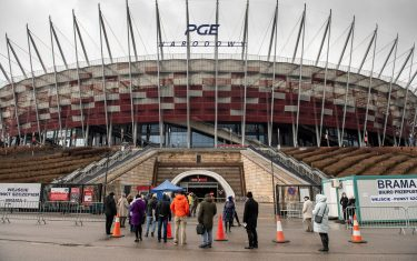 Visitors at an entrance to a Covid-19 vaccination center in Poland's National Stadium in Warszawa, Poland, on Friday, March 12, 2021. Eastern Europe is struggling to contain a growing wave of coronavirus infections, even as an accelerating global vaccine rollout is raising optimism about the end of the pandemic. Photographer: Lukasz Sokol/Bloomberg via Getty Images