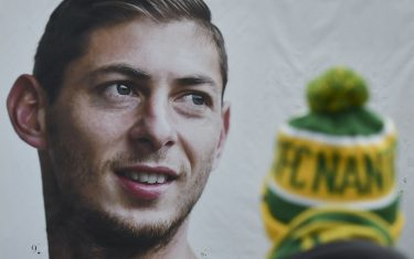 A person stands in front of a portrait of Nantes' Argentinian forward Emilianio Sala, who died one year ago in a plane crash, ahead of the French L1 football match between FC Nantes and Bordeaux in front of the La Beaujoire stadium in Nantes, western France, on January 26, 2020. - The 28-year-old striker was killed when the small plane taking him to join the then Premier League club Cardiff after being bought from Nantes crashed off the Channel island of Guernsey. (Photo by Sebastien SALOM-GOMIS / AFP) (Photo by SEBASTIEN SALOM-GOMIS/AFP via Getty Images)