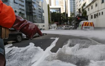 SAO PAULO, BRAZIL - MARCH 23: A member of a cleaning crew disinfects the streets around the Sirio-Libanes Hospital on March 23, 2020 in Sao Paulo, Brazil. These measures are aimed at stopping the spreading of the coronavirus (COVID-19) pandemic. According to the Ministry of Health, as of Monday, March 23, Brazil has 1.891 confirmed cases of the coronavirus (COVID-19) and at least 34 recorded deaths. (Photo by Miguel Schincariol/Getty Images)