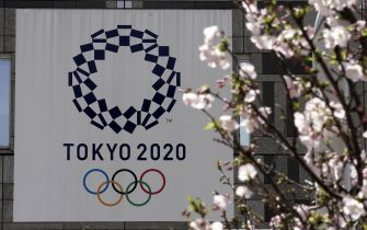 epa08338045 The logo of the Tokyo 2020 Olympic Games hangs from a wall behind cherry blossoms in Tokyo, Japan, 02 April 2020. Tokyo Governor Yuriko Koike warned the city is going through an important phase in preventing further spread of COVID-19. The Tokyo 2020 Olympics organizing committee and the International Olympic Committee (IOC) announced on 30 March 2020 that the Games would be rescheduled to 23 July 2021 amid the ongoing coronavirus pandemic that forced the event's one year postponement.  EPA/KIMIMASA MAYAMA