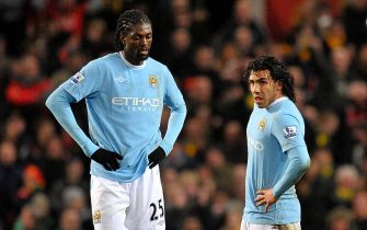 Manchester City's Carlos Tevez (right) and Emmanuel Adebayor (left) dejected in the center circle after Manchester United score a late goal