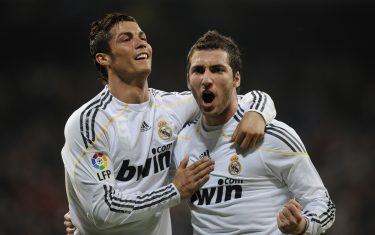 Real Madrid's Argentinian forward Gonzalo Higuain (R) celebrates with Portuguese forward Cristiano Ronaldo after scoring against Sporting Gijon during their Spanish League football match at Santiago Bernabeu stadium in Madrid on March 20, 2010.    AFP PHOTO/ PIERRE-PHILIPPE MARCOU (Photo credit should read PIERRE-PHILIPPE MARCOU/AFP via Getty Images)