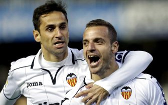 epa03515946 Forward of Valencia, Roberto Soldado (R) celebrates with his teammate Jonas Goncalvez (L) the goal he scored against Getafe, during the match between Valencia and Getafe played at Mestalla stadium in Valencia, eastern Spain, 21 December 2012.  EPA/JUAN CARLOS CARDENAS
