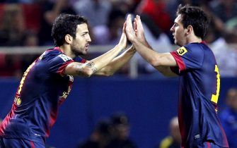 epa03415711 A picture made available on 30 September 2012 shows FC Barcelona's Argentinian striker Leo Messi (R) congratulating his team mate Cesc Fabregas after scoring the first goal against Sevilla during their match of the Spanish Primera Division League held at Sanchez Pizjuan stadium in Sevilla, southern Spain, 29 September 2012. Barcelona won 3-2.  EPA/JULIO MUNOZ