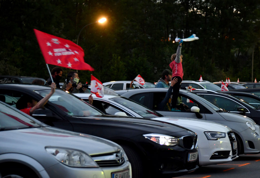 Football fans follow the Austrian Cup final between FC Red Bull Salzburg and SC Austria Lustenau on a giant screen from their cars at a drive-in in Salzburg on May 29, 2020. (Photo by BARBARA GINDL / APA / AFP) / Austria OUT (Photo by BARBARA GINDL/APA/AFP via Getty Images)