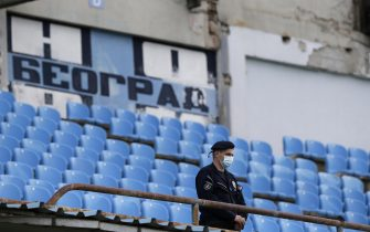 epa08453144 A police officer wearing a protective face mask stands guard during the Serbian SuperLiga soccer match between Rad and Red Star in Belgrade, Serbia, 29 May 2020. The Serbian SuperLiga resumes without spectators after a suspension because of the coronavirus pandemic.  EPA/ANDREJ CUKIC