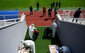 Kosovar football referees get tested for COVID-19 by medical staff wearing protective suits at the Fadil Vokrri Stadium in Pristina on May 30, 2020. - Since March 14, all sporting events have been postponed in Kosovo, due to the risk of the Coronavirus pandemic. (Photo by Armend NIMANI / AFP) (Photo by ARMEND NIMANI/AFP via Getty Images)