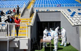Medical staff wearing protective suits prepare to test Kosovar football referees for COVID-19 at the Fadil Vokrri Stadium in Pristina on May 30, 2020. - Since March 14, all sporting events have been postponed in Kosovo, due to the risk of the Coronavirus pandemic. (Photo by Armend NIMANI / AFP) (Photo by ARMEND NIMANI/AFP via Getty Images)