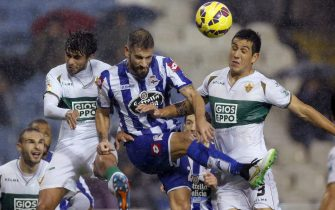 Deportivo Coruna's defender Alberto Lopo (C) heads for the ball with Elche CF's defenders, Chilean Enzo Roco (L) and Jose Angel Alonso (R) during the Spanish Liga Primera Division soccer match played at the Riazor stadium, in A Coruna, northwestern Spain, 15 December 2014. EFE/Cabalar