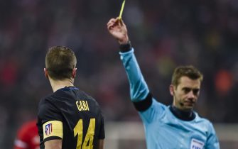 French referee Clement Turpin shows Atletico Madrid's Spanish midfielder Gabi the yellow card during the UEFA Champions League group D football match between FC Bayern Munich and Atletico Madrid in Munich, southern Germany, on December 6, 2016.  / AFP / GUENTER SCHIFFMANN        (Photo credit should read GUENTER SCHIFFMANN/AFP via Getty Images)