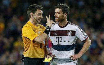 epa04735850 Bayer Munich's midfielder Xabi Alonso (R) receives a yellow card from Italian referee Nicola Rizzoli (L) during the first leg of the UEFA Champions League semifinal match FC Barcelona against Bayer Munich played at Nou Camp stadium in Barcelona, Catalonia, Spain, 6 May 2015.  EPA/ANDREU DALMAU