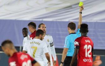 epa08507258 Real Madrid's defender Sergio Ramos (L) is booked with a yellow card by referee Mario Melero Lopez during the Spanish LaLiga match between Real Madrid and RCD Mallorca at Alfredio Di Stefano stadium in Madrid, Spain, 24 June 2020.  EPA/JUANJO MARTIN