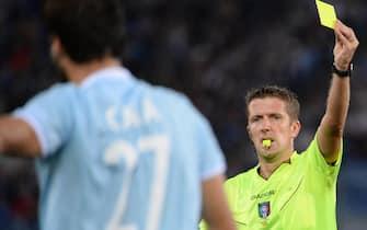 Italian referee Daniele Orsato (R) shows the yellow card to Lorik Cana of SS Lazio, during the Italian Serie A soccer match, between SS Lazio and ACF Fiuorentina at the Olimpico stadium in Rome, Italy, 22 September 2013.  ANSA / MAURIZIO BRAMBATTI