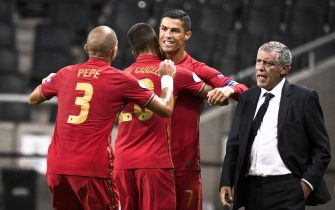 epa08655216 Portugal's Christiano Ronaldo is congratulated on his 100th goal for the national team by Pepe and Joao Cancelo and national team captain Fernando Santo (R) during the UEFA Nations League, division A, group 3 soccer game betwween Sweden and Portugal at Friends Arena in Stockholm, Sweden, 08 September 2020.  EPA/CLAUDIO BRESCANI SWEDEN OUT