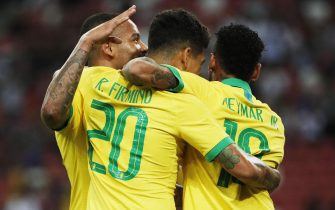 epa07909915 Roberto Firmino (C) of Brazil celebrates with his teammates Gabriel Jesus (L) and Neymar Jr. (R) after scoring the first goal during an international friendly match between Brazil and Senegal at the National Stadium in Singapore, 10 October 2019.  EPA/WALLACE WOON