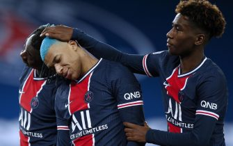 epa08888987 Paris Saint Germain's Kylian Mbappe (C) reacts with teammates Moise Kean (L) and Timothee Pembele (R) after scoring the 1-0 goal during the French Ligue 1 soccer match between PSG and Lorient at the Parc des Princes stadium in Paris, France, 16 December 2020.  EPA/YOAN VALAT