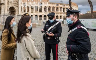 ROME, ITALY - DECEMBER 24: Carabinieri at the Colosseum checking two tourists during the first day of lockdown on Christmas Eve on December 24, 2020 in Rome, Italy. Italy will remain under a nationwide lockdown over the Christmas period, as authorities seek to avoid further spikes in coronavirus infections. Italy, currently in a second wave, is still one of Europe's worst hit countries with 1.98 million people infected with the virus. (Photo by Fabrizio Villa/Getty Images)