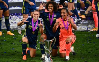 SAN SEBASTIAN, SPAIN - AUGUST 30: Eugenie Le Sommer, Wendie Renard and Sarah Bouhaddi of Olympique Lyon celebrate with the UEFA Women's Champions League Trophy following their team's victory in the UEFA Women's Champions League Final between VfL Wolfsburg Women's and Olympique Lyonnais at Estadio Anoeta on August 30, 2020 in San Sebastian, Spain. (Photo by Gabriel Bouys/Pool via Getty Images)