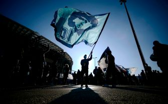 "A man waves a flag at the effigy of late Argentinian football legend Diego Maradona, as people gather on November 26, 2020 outside the San Paolo stadium in Naples to mourn the death of Maradona. - Maradona, widely remembered for his ""Hand of God"" goal against England in the 1986 World Cup quarter-finals, died on November 25, 2020 of a heart attack at his home near Buenos Aires in Argentina, while recovering from surgery to remove a blood clot on his brain. (Photo by Filippo MONTEFORTE / AFP) (Photo by FILIPPO MONTEFORTE/AFP via Getty Images)"