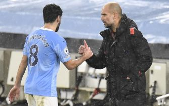 epa08905269 Manchester City's Ilkay Gundogan (L) shakes hands with manager Pep Guardiola (R) during the English Premier League soccer match between Manchester City and Newcastle United in Manchester, Britain, 26 December 2020.  EPA/Peter Powell / POOL EDITORIAL USE ONLY. No use with unauthorized audio, video, data, fixture lists, club/league logos or 'live' services. Online in-match use limited to 120 images, no video emulation. No use in betting, games or single club/league/player publications.