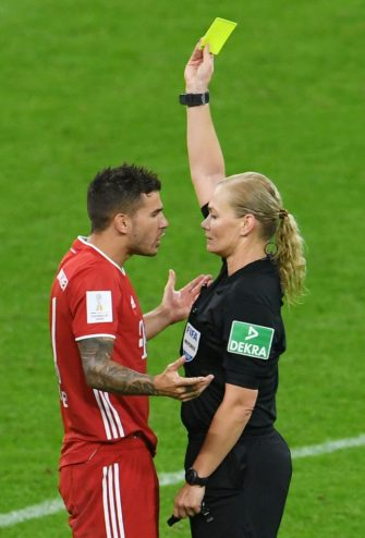 Bayern Munich's French defender Lucas Hernandez is shown a yellow card by the referee Bibiana Steinhaus during the German Supercup football match FC Bayern Munich v BVB Borussia Dortmund in Munich, Southern Germany, on September 30, 2020. (Photo by ANDREAS GEBERT / POOL / AFP) / DFL REGULATIONS PROHIBIT ANY USE OF PHOTOGRAPHS AS IMAGE SEQUENCES AND/OR QUASI-VIDEO (Photo by ANDREAS GEBERT/POOL/AFP via Getty Images)