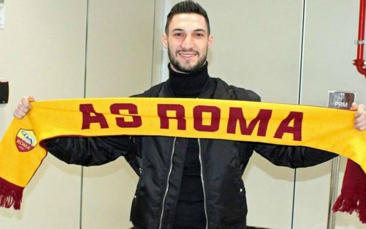 Politano posa con una sciarpa della Roma all'arrivo a Fiumicino