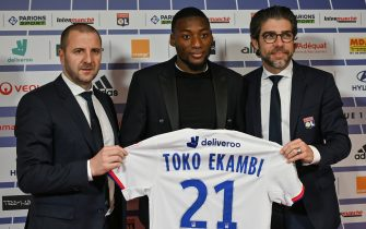 Olympique Lyonnais's newly recruited Cameroonian forward Karl Toko Ekambi (C) poses with his jersey next to Head of Lyon's recruitment unit Florian Maurice (L) and Olympique Lyonnais Brazilian sports director Juninho (R), during a press conference on January 21, 2020, at the Groupama Stadium in Decines-Charpieu near Lyon, central-eastern France. (Photo by PHILIPPE DESMAZES / AFP) (Photo by PHILIPPE DESMAZES/AFP via Getty Images)