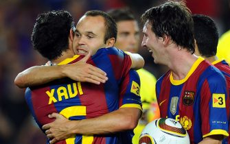 Barcelona's midfielder Andres Iniesta (C), Barcelona's midfielder Xavi Hernandez (L) and Barcelona's Argentinian forward Lionel Messi (R) celebrate after winning the Supercup trophy after a second leg football match against Sevilla on August 21, 2010 at Camp Nou stadium in Barcelona. AFP PHOTO/LLUIS GENE (Photo credit should read LLUIS GENE/AFP via Getty Images)