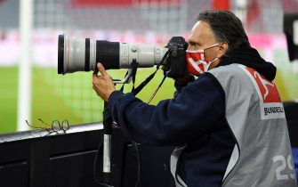 epa08440064 A photographer wears a protective face mask during the German Bundesliga soccer match Bayern Munich vs Eintracht Frankfurt in Munich, Germany, 23 May 2020. The German Bundesliga is the world's first major soccer league to resume after a two-month suspension because of the Coronavirus pandemic.  EPA/ANDREAS GEBERT / POOL DFL regulations prohibit any use of photographs as image sequences and/or quasi-video.