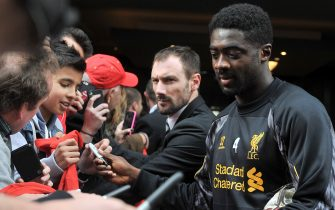 Liverpool defender Kolo Toure (R) signs autographs for fans as the team leaves their hotel for a football training session in Melbourne on July 22, 2013.  AFP PHOTO / Paul CROCK        (Photo credit should read PAUL CROCK/AFP via Getty Images)
