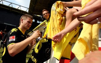 DORTMUND, GERMANY - JULY 04: Lukasz Piszczek signs autographs after the Borussia Dortmund first training session for the upcoming season 2010/2011 at the Signal Iduna Park on July 4, 2010 in Dortmund, Germany.  (Photo by Alex Grimm/Bongarts/Getty Images)