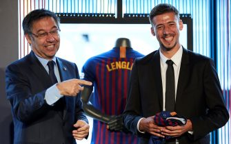 epa06886137 French midfielder Clement Lenglet (R) poses during his presentation as new player of the Barcelona FC next to the club's President, Josep Maria Bartomeu (L), at Camp Nou stadium in Barcelona, Spain, 13 July 2018. Lenglet has signed with the club until June 2023.  EPA/Alejandro Garcia