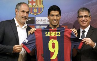 epa04359757 Uruguayan striker Luis Suarez (C) poses with a FC Barcelona shirt with his name and number during his official presentation with the club next to sports director Andoni Zubizarreta (L) and sports vicepresident Jordi Mestre (R), five weeks after signing for his new team in Barcelona, northeastern Spain, 19 August 2014.  EPA/Toni Albir