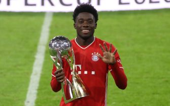 epa08710702   Alphonos Davies of FC Bayern Munchen celebrates with the Supercup trophy after the Supercup 2020 match between FC Bayern Munchen and Borussia Dortmund at Allianz Arena in Munich, Germany, 30 September 2020.  EPA/Alexander Hassenstein / POOL CONDITIONS - ATTENTION: The DFL regulations prohibit any use of photographs as image sequences and/or quasi-video.