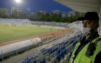 epa08463540 A steward wearing a protective face mask on duty during the match between Partizani and Skenderbeu valid for the Albanian football league in Tirana, Albania, 03 June 2020. The Albanian Footbal Federation decided to restart the footbal matches under some restricted measures after 3 months of interruptions due to Coronavirus Covid-19.  EPA/Malton Dibra