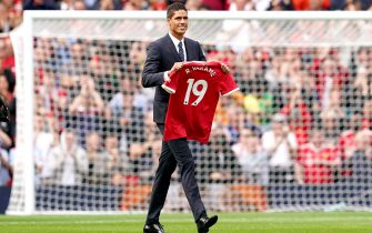 Manchester United's Raphael Varane holds up his shirt on the pitch as is is confirmed that he has signed for the club on a four-year deal ahead of the Premier League match at Old Trafford, Manchester. Picture date: Saturday August 14, 2021.