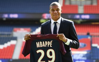 TOPSHOT - Paris Saint-Germain's new forward Kylian Mbappe holds his jersey during his presentation at the Parc des Princes stadium in Paris on September 6, 2017.The 18-year-old striker moved to PSG in a season-long loan deal with a 180 million euro buy-out clause attached, making him the second most expensive player of all time behind new teammate Neymar. / AFP PHOTO / FRANCK FIFE        (Photo credit should read FRANCK FIFE/AFP/Getty Images)