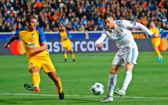 Real Madrid's Portuguese forward Cristiano Ronaldo (R) shoots to score as he is marked by Apoel's Spanish midfielder Jesus Rueda (L) during the UEFA Champions League Group H match between Apoel FC and Real Madrid on November 21, 2017, in the Cypriot capital Nicosia's GSP Stadium.  / AFP PHOTO / Jack GUEZ        (Photo credit should read JACK GUEZ/AFP via Getty Images)