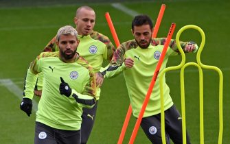 Manchester City's Argentinian striker Sergio Aguero (L), Manchester City's Spanish defender Angelino (C) and Manchester City's Portuguese midfielder Bernardo Silva (R) attend a team training session at City Football Academy in Manchester, north west England on October 21, 2019, on the eve of their UEFA Champions League football Group C match against Atalanta. (Photo by Paul ELLIS / AFP) (Photo by PAUL ELLIS/AFP via Getty Images)