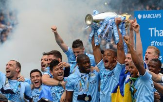 Manchester City's Belgian midfielder Vincent Kompany (C) celebrates with the Premiership trophy after winning 2-0 during the English Premier League football match between Manchester City and West Ham United at the Etihad Stadium in Manchester on May 11, 2014.  AFP PHOTO/ANDREW YATES - RESTRICTED TO EDITORIAL USE. No use with unauthorized audio, video, data, fixture lists, club/league logos or live services. Online in-match use limited to 45 images, no video emulation. No use in betting, games or single club/league/player publications.        (Photo credit should read ANDREW YATES/AFP via Getty Images)