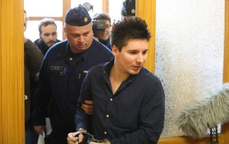 Football Leaks whistleblower Rui Pinto (R) is escorted by a judicial officer as he arrives at the Metropolitan Court in Budapest, Hungary, for his trial on March 5, 2019. - The court has approved the extradition of the Portuguese hacker linked to the Football Leaks website that has exposed alleged corruption, sparking investigations in several European countries. (Photo by FERENC ISZA / AFP)        (Photo credit should read FERENC ISZA/AFP via Getty Images)