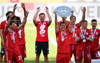 epa08513178 Robert Lewandowski (C) of Bayern Munich lifts the trophy to celebrate the German soccer championship title following the Bundesliga match between VfL Wolfsburg and Bayern Munich in Wolfsburg, Germany, 27 June 2020.  EPA/STUART FRANKLIN / POOL CONDITIONS - ATTENTION: The DFL regulations prohibit any use of photographs as image sequences and/or quasi-video.
