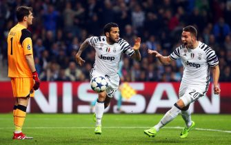 epa05809465 Juventus' Dani Alves (C) celebrates with his teammate Marko Pjaca (R) after scoring the 2-0 lead against FC Porto's goalkeeper Iker Casillas (L) during the UEFA Champions League round of 16, first leg soccer match between FC Porto and Juventus FC at Dragao stadium in Porto, Portugal, 22 February 2017.  EPA/JOSE COELHO