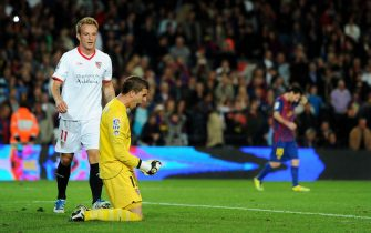 BARCELONA, SPAIN - OCTOBER 22: Goalkeeper Javi Varas of Sevilla FC celebrates on his knees besides his teammate Ivan Rakitic (L) as Lionel Messi (R) of FC Barcelona trudges off the pitch at the end of the la Liga match between FC Barcelona and Sevilla FC at the Camp Nou stadium on October 22, 2011 in Barcelona, Spain.  (Photo by Jasper Juinen/Getty Images)