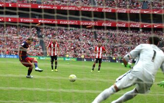 epa04895143 FC Barcelona's Lionel Messi (L) misses a penalty kick against Athletic Club's goalkeeper Gorka Iraizoz (R) during the Spanish Primera Division soccer match between Athletic Club and FC Barcelona at San Mames stadium, in Bilbao, Spain, 23 August 2015.  EPA/LUIS TEJIDO