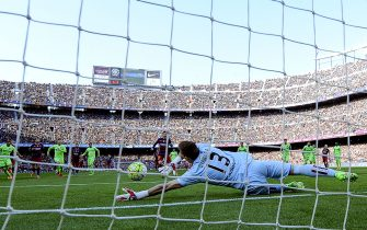 Getafes goalkeeper Vicente Guaita (front) stops a penalty kick shot by Barcelona's Argentinian forward Lionel Messi (farC) during the Spanish league football match FC Barcelona vs Getafe CF at the Camp Nou stadium in Barcelona on March 12, 2016.     / AFP / JOSEP LAGO        (Photo credit should read JOSEP LAGO/AFP via Getty Images)