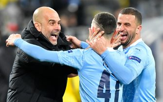 """14 April 2021, North Rhine-Westphalia, Dortmund: Football: Champions League, knockout round, quarter-finals, second leg, Borussia Dortmund - Manchester City at Signal Iduna Park. Manchester's Phil Foden (M) celebrates with Manchester teammates Kyle Walker (r) and Manchester coach Josep """"Pep"""" Guardiola (l) after scoring the 1:2 goal. Photo: Martin Meissner/AP-Pool/dpa"""