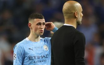 epa09235975 Phil Foden (L) and manager Josep Guardiola of Manchester City react after the UEFA Champions League final between Manchester City and Chelsea FC in Porto, Portugal, 29 May 2021.  EPA/Carl Recine / POOL